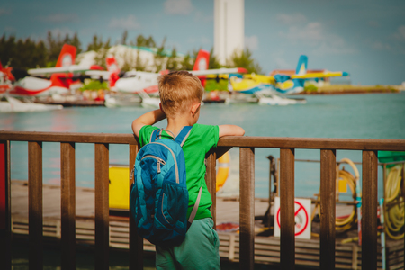 little boy looking at seaplanes in Maldives