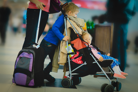 mother with kids and luggage wait in airport, family travel Imagens