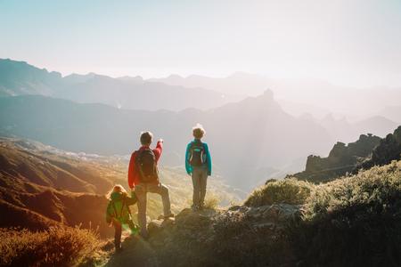 Il padre con i bambini viaggia tra le montagne del tramonto, fa escursioni in famiglia nella natura Archivio Fotografico