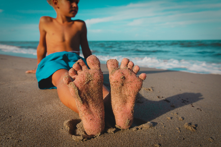 little boy relax at summer beach, focus on feet Foto de archivo