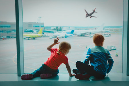 kids looking at plane in airport, family travel