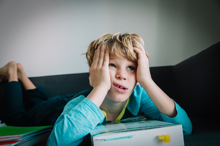little boy tired of reading, kid bored of doing homework
