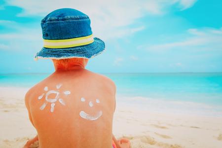 kleiner Junge des Sonnenschutzes mit Sonnencreme am tropischen Strand