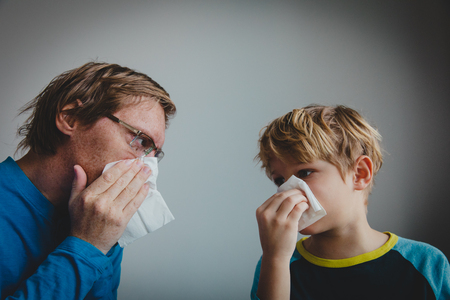 father and son wiping and blowing nose, infection or allergy