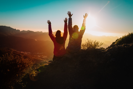 Silhouettes of happy couple enjoy travel at sunset mountains Stock Photo