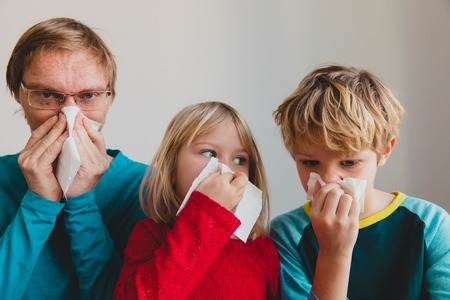 father and kids wiping and blowing nose, infection or allergy