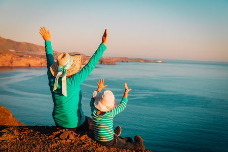 mother and little daughter enjoy travel in mountains at sea