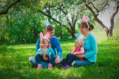 happy mom and dad with kids on easter eggs hunt in spring