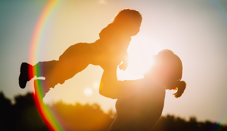 mother and little daughter play at sunset sky, family love concept