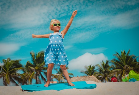 happy little girl play with surf board on beach, child enjoy vacation Stockfoto