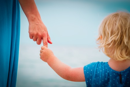 mother and little daughter holding hands on beach, family vacation