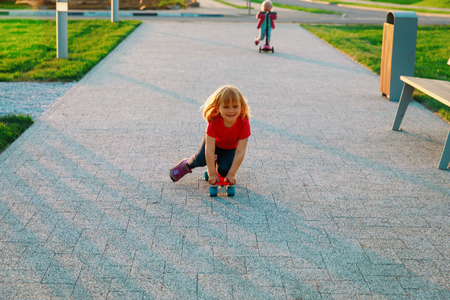 kids on skate board and scooter riding outside