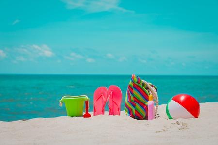 bag, suncream, toys and flip flops on beach Stock Photo