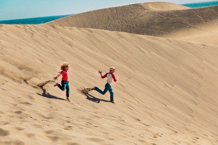 happy boy and girl play in sand dunes