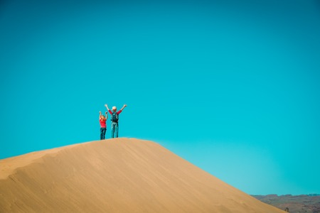 happy boy and girl have fun in sand dunes