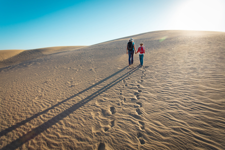mother and son walk in sand dunes, leaving footprints in sand Foto de archivo