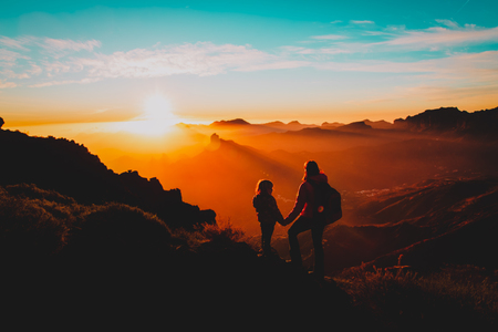 mother with little daughter enjoy travel in sunset mountains