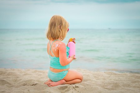 sun protection concept - little girl with suncream at beach