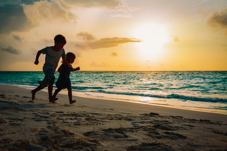 little boy and girl run play at sunset beach
