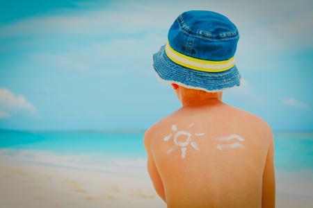 sun protection- little boy with suncream at tropical beach Stok Fotoğraf