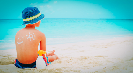 sun protection- little boy with suncream at beach