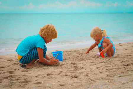little boy and girl play with sand on beach Foto de archivo