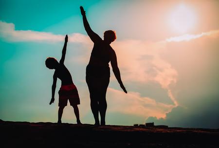 Schattenbild des Familienspiels am Sonnenunterganghimmel