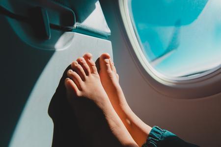 pies de niña viajan en avión, niño en vuelo, seguridad Foto de archivo