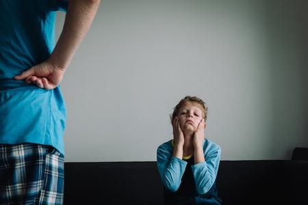 zły rodzic patrzący na zmęczonego, zawstydzonego i wyczerpanego dzieciaka