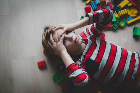 kid tired of playing, exhaustion with toys scattered around Banco de Imagens