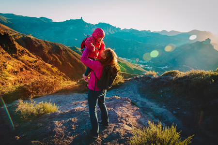mom with little daughter enjoy travel in sunset mountains Standard-Bild - 121390999