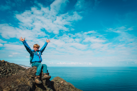 happy young boy with backpack hiking in mountains at sea