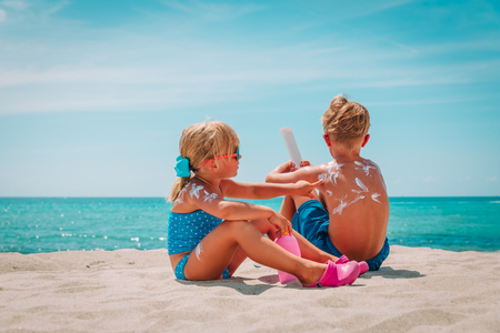 sun protection, little girl and boy with sun cream at beach Stock fotó