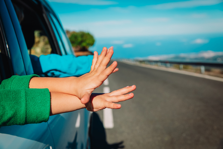 hands of happy family travel by car on road in nature 版權商用圖片