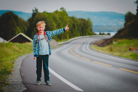 cute boy with backpack travel along the road, showing sign waiting car Stock Photo