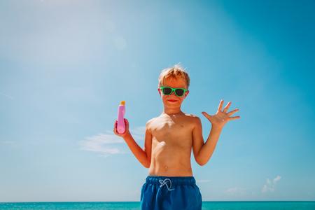 sun protection- happy boy with suncream at beach