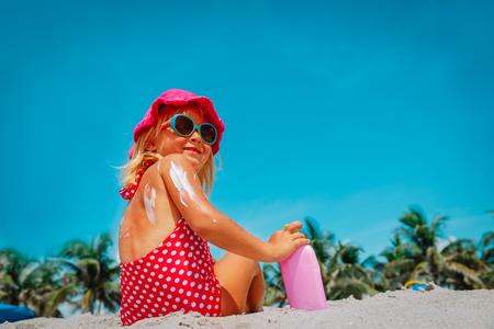 Sonnenschutzkonzept - süßes Mädchen mit Sonnencreme am Strand