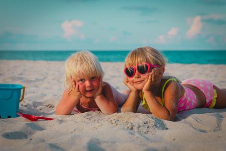 귀여운 행복한 어린 소녀들이 해변에서 모래를 가지고 노는