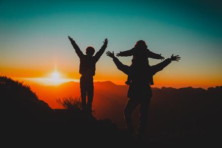 Glücklicher Vater und Kinder wandern in den Sonnenuntergangsbergen