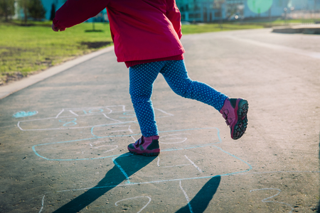 little girl play hopscotch on urban playground