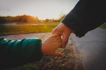 grootmoeder houdt kleinkind hand in de natuur, opvoedingsconcept
