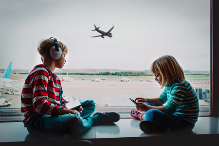 boy and girl with mobile phone and touch pad waiting in airport Stock Photo