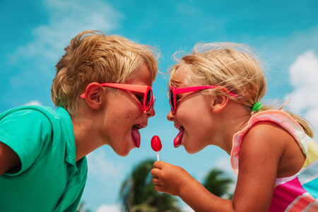 happy little girl and boy with lollipop on summer vacation Stock Photo