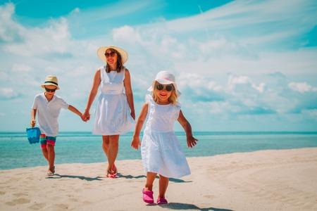 moeder met zoon en dochter lopen op strand Stockfoto
