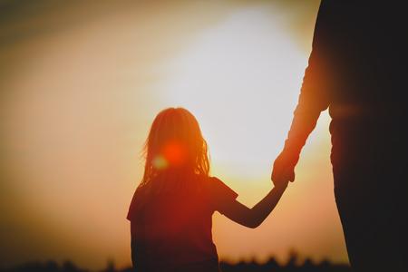Schattenbild des kleinen Mädchens, das Elternhand bei Sonnenuntergang hält
