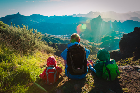 father and kids travel in sunset mountains