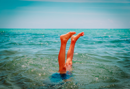 child making handstand in sea, kids vacation fun Stockfoto