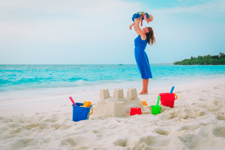 family beach vacation- sand castle and happy mother and child at sea