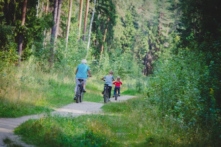 active senior grandmother with kids riding bikes in nature