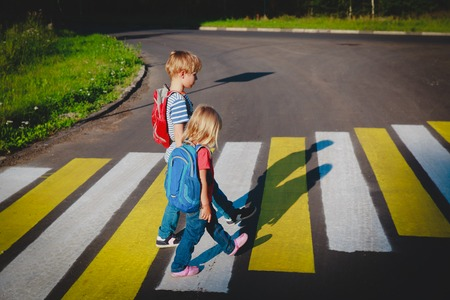 little boy and girl holding hands go to school